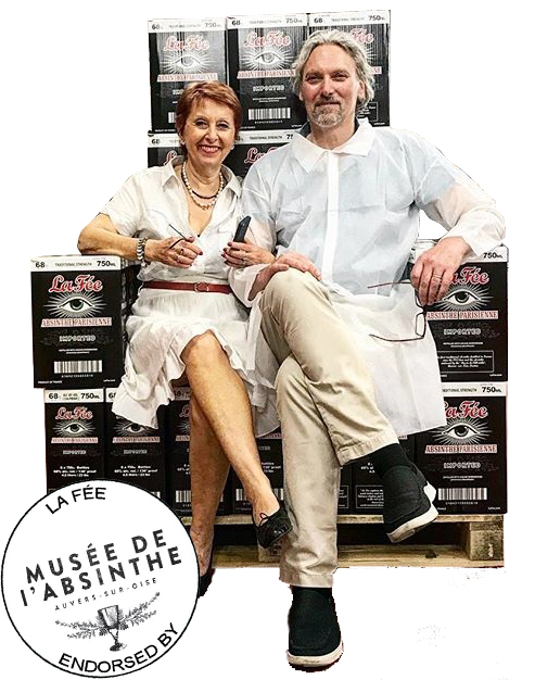 George Rowler & Marie-Claude Delahaye sitting on a throne made of boxes of La Fée Blanche Absinthe